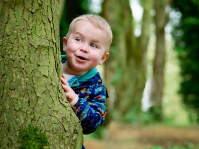 Boy toddler playing hide and seek with family photographer Alexandra Tandy Photography