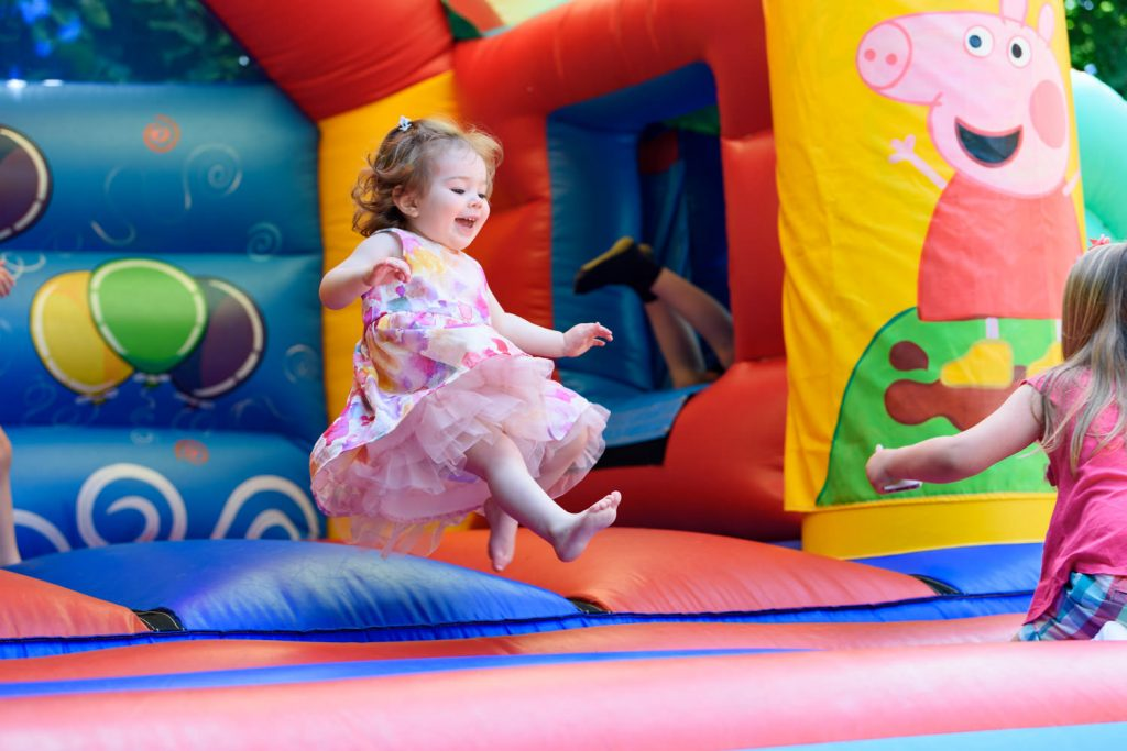 Girl bouncing on bouncy castle photographed by Alexandra Tandy Photography CHILDREN'S  party photographer