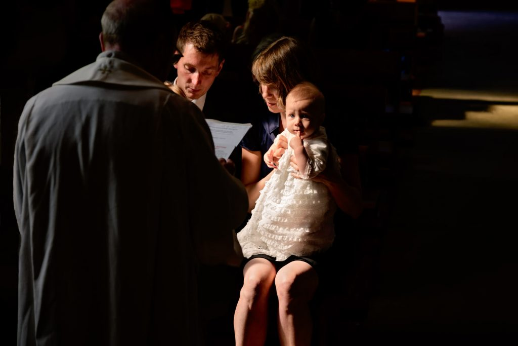 Alexandra Tandy Photography baby at baptism looking at Priest