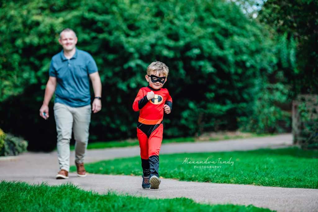 Boy walking along in Incredibles costume