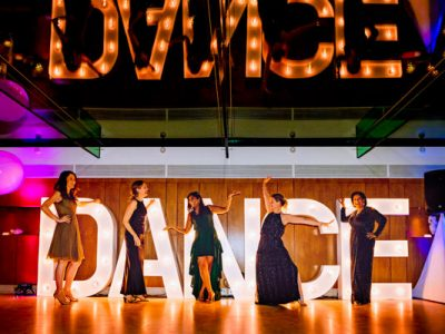 Ladies dancing in front of giant illuminated letters spelling dance