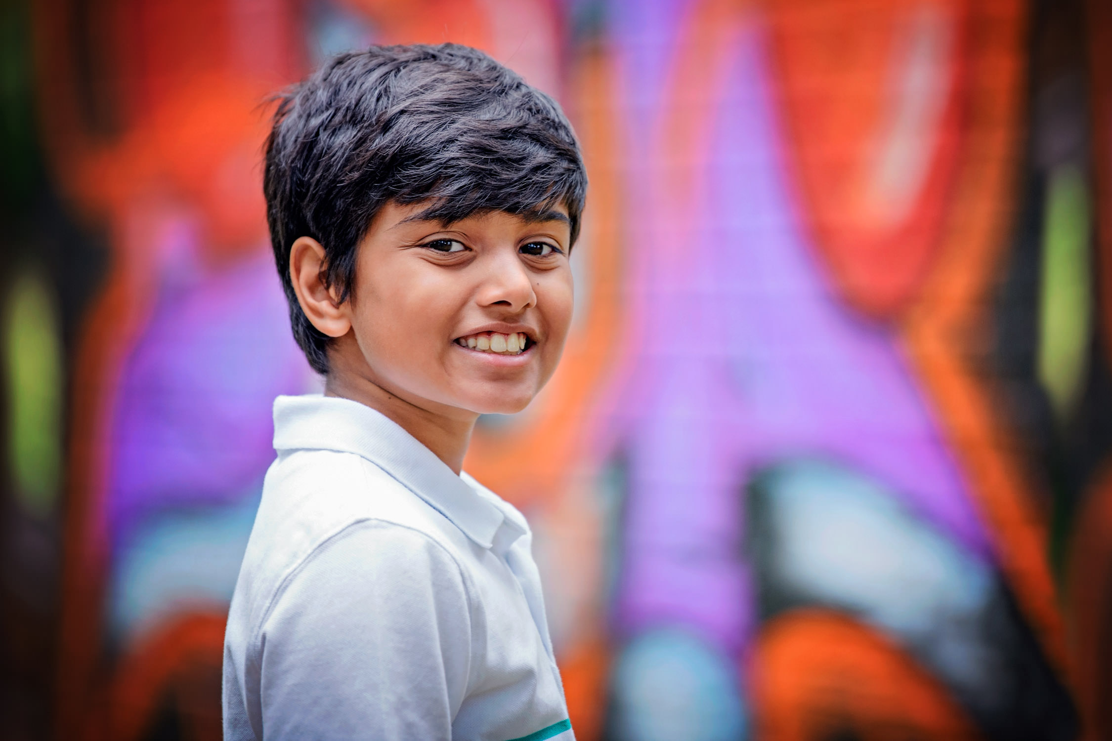 Boy standing in front of colourful grafitti