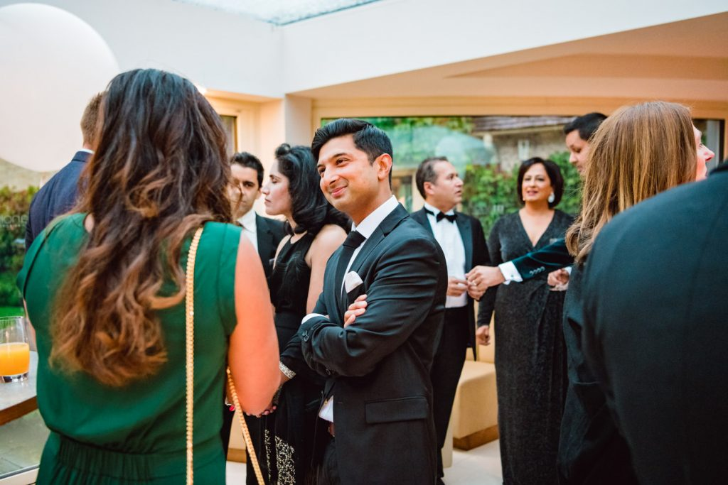 Male guest listening to fellow guest at Le Manoir aux Quat'Saisons party photographed by an event photographer