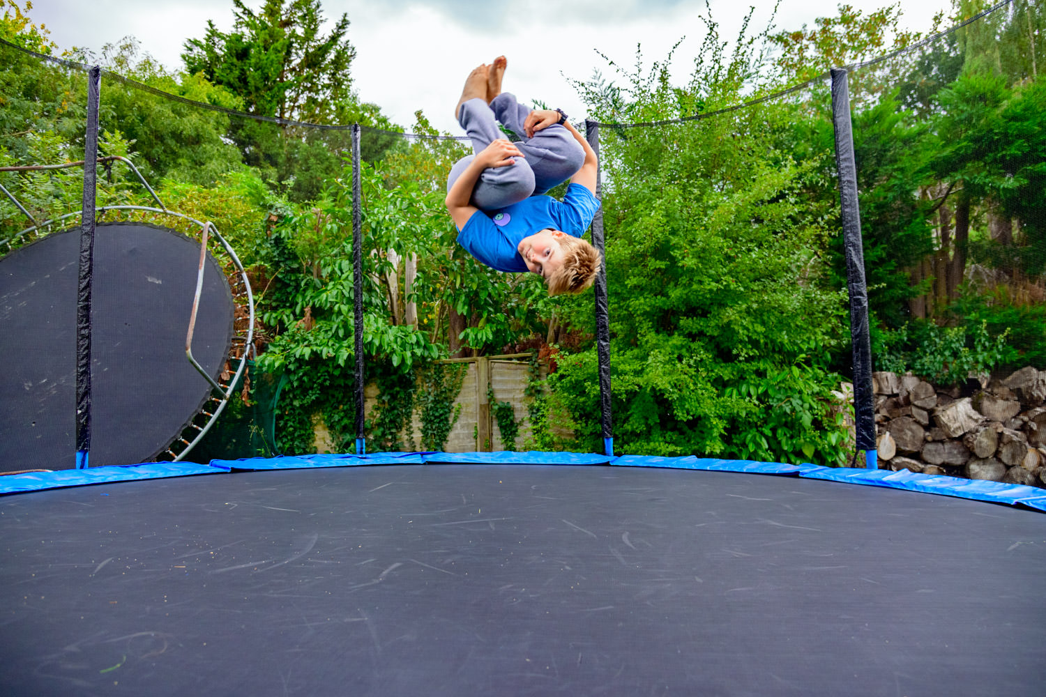 Boy suspended mid air as he does a somersault on the trampoline