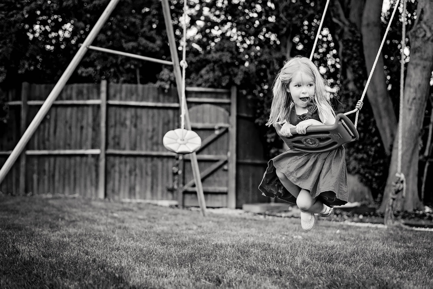 Girl leaning over a swing on her tummy and lifting her legs as she swings