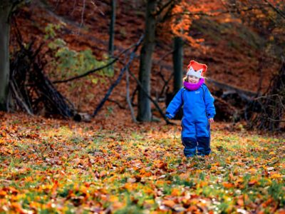 Girl standing in autumnal leaves at Blenheim Palace