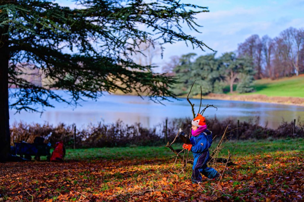Young girl walking at beside Blenheim Palace lake in the autumnal leaves