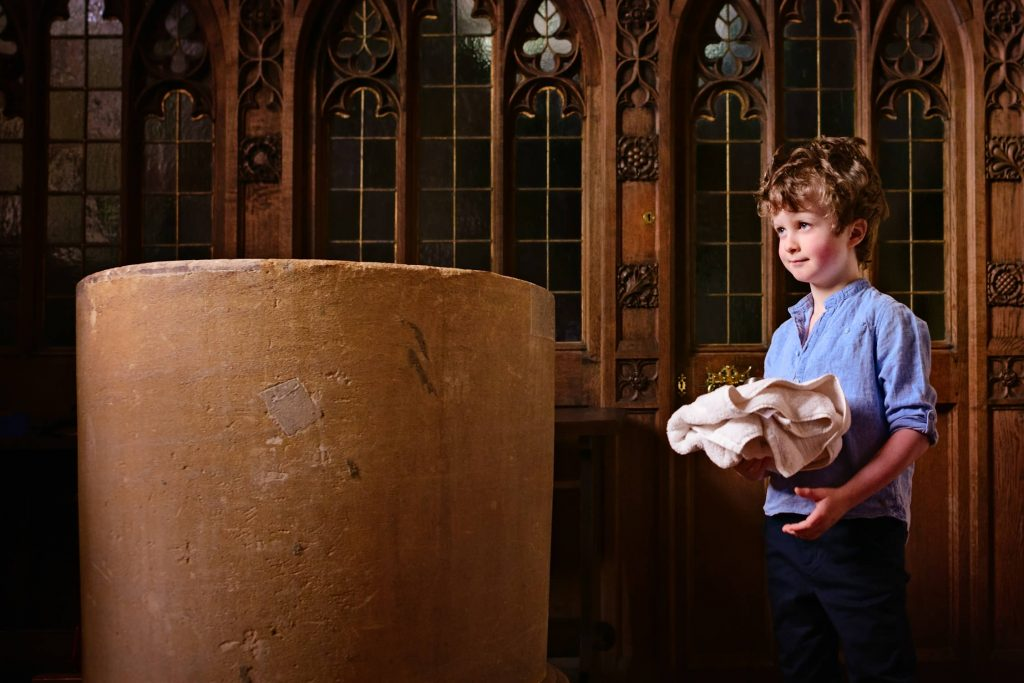 Boy standing by the font with christening towel