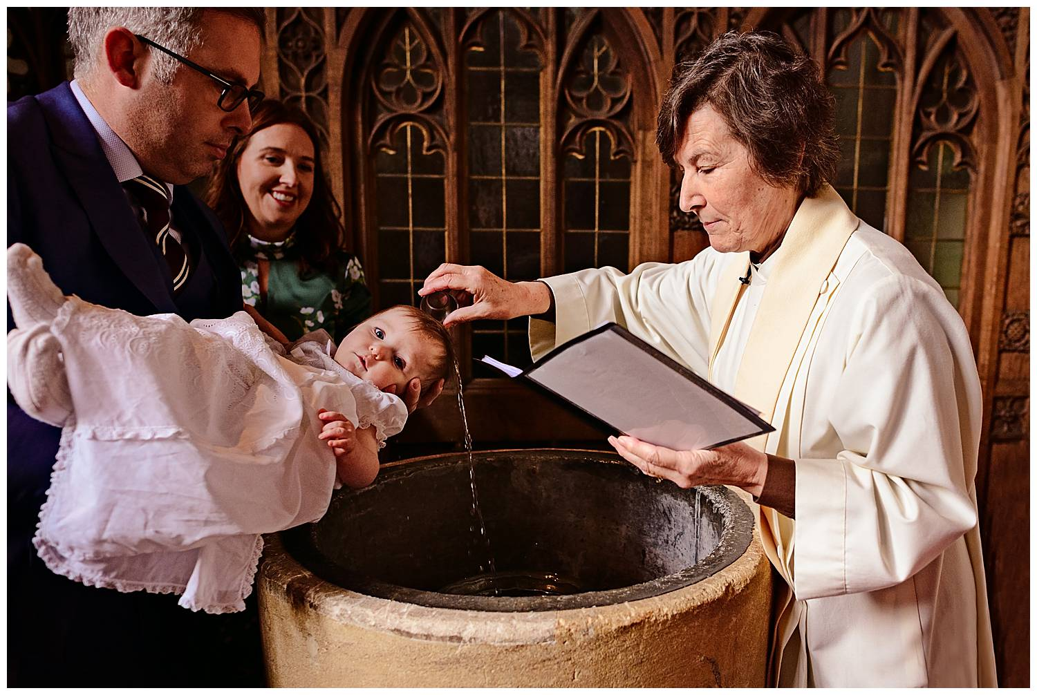 Baby being christening and looking directly into the camera as vicar pours water over it's head