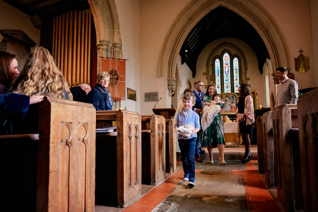 Boy carrying christening towel to the church font