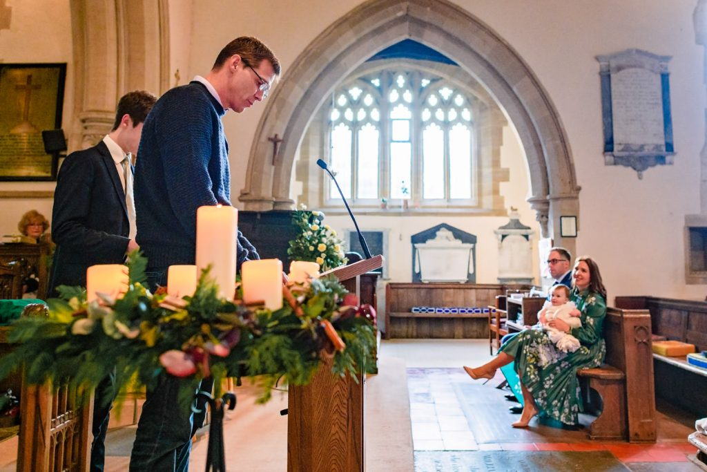 Godfather giving reading at christening service