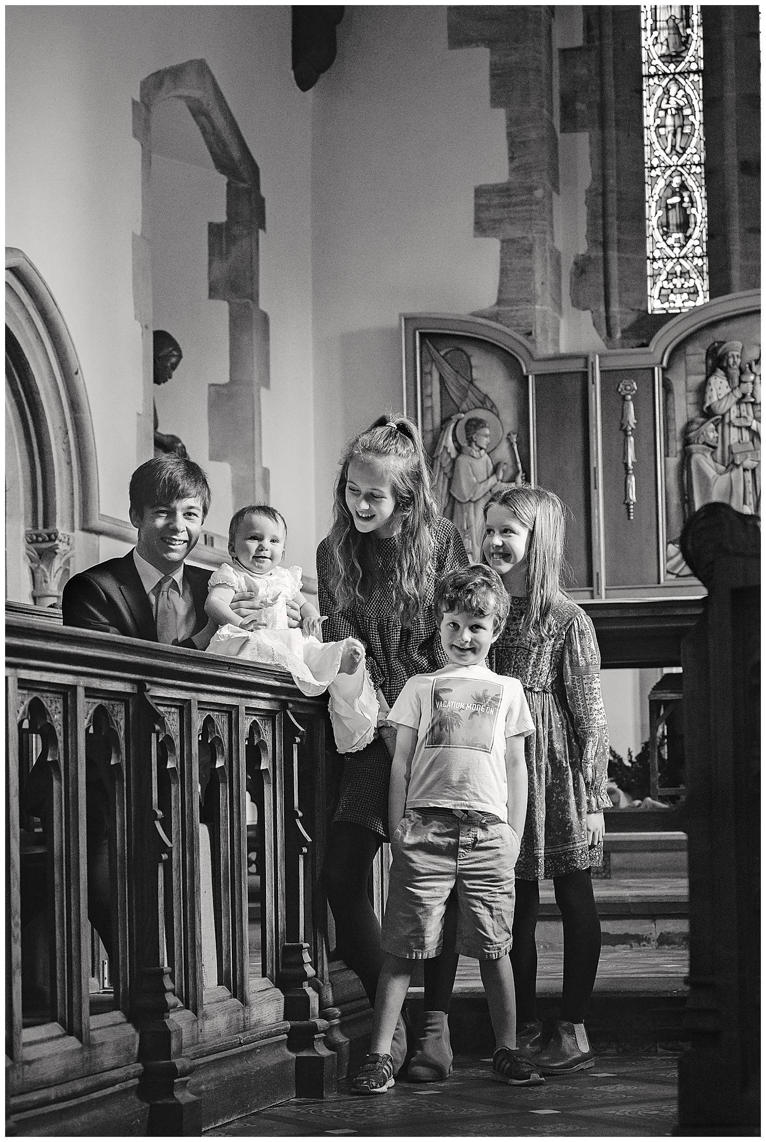 Four children standing in church looking at their new baby cousin who is about to be christened