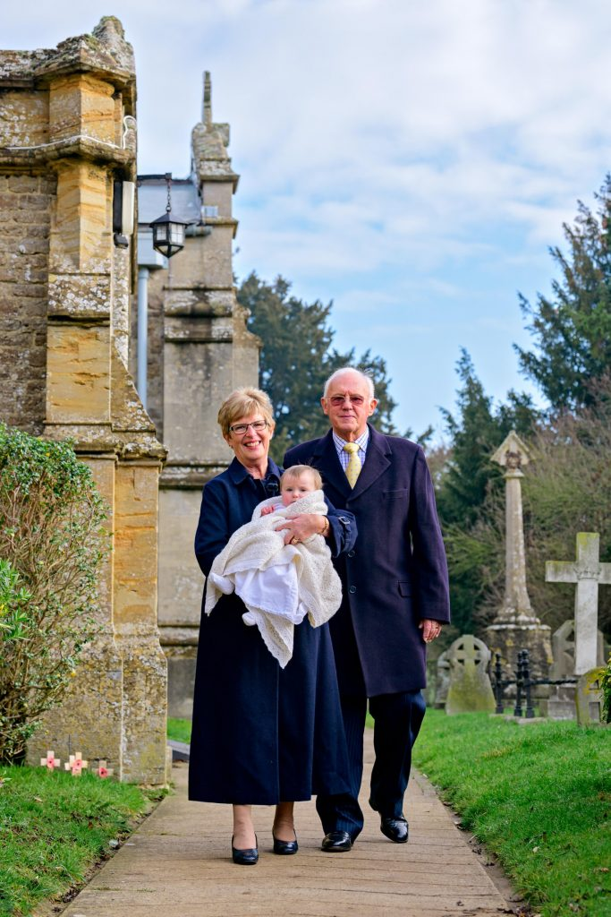 Grandparents walking towards Oxford Christening Photographer holding baby in her christening gown