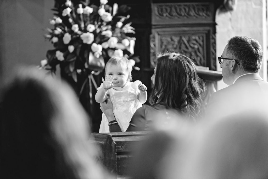 Baby waving at congregation at her christening