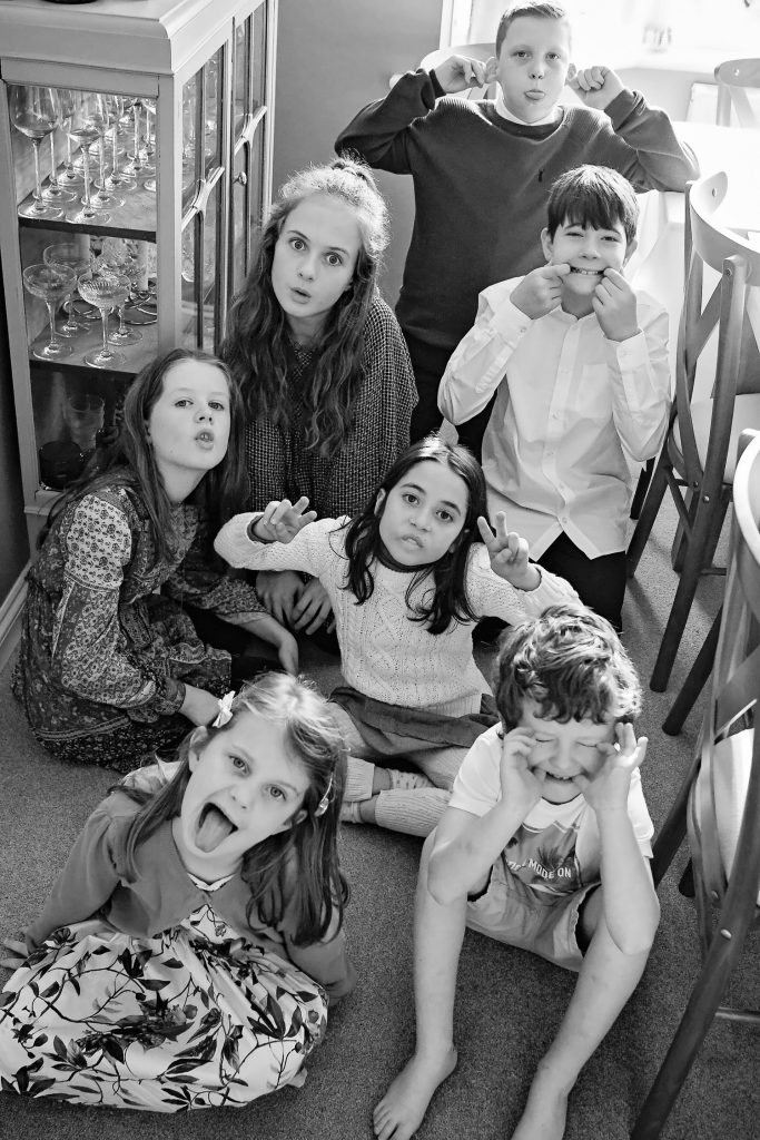 seven children pulling funny faces at the camera