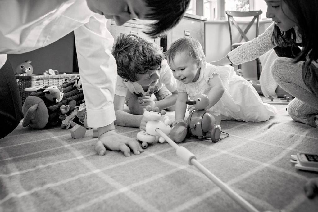 Baby crawling on the floor with other children playing