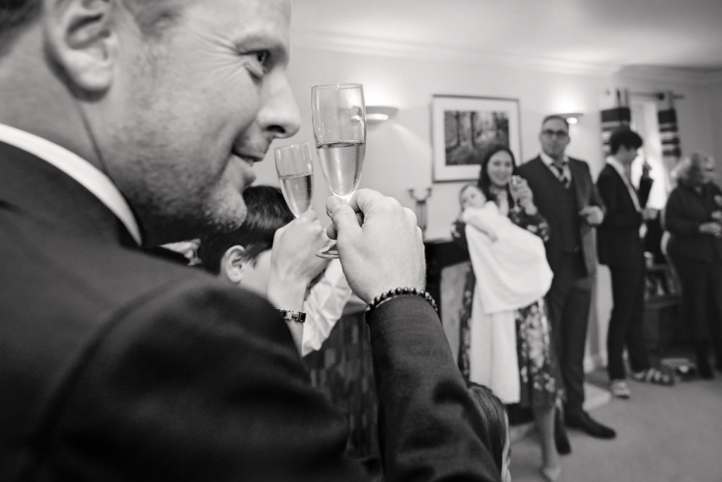 Man raising champagne glass up to toast baby's christening