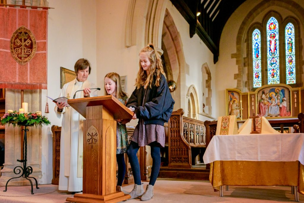 Two girls giving a reading at church service