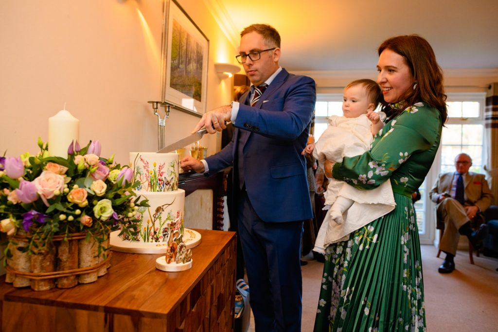 parents cutting baby's christening cake