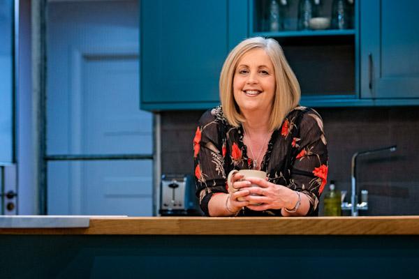 Lady stood in a blue kitchen