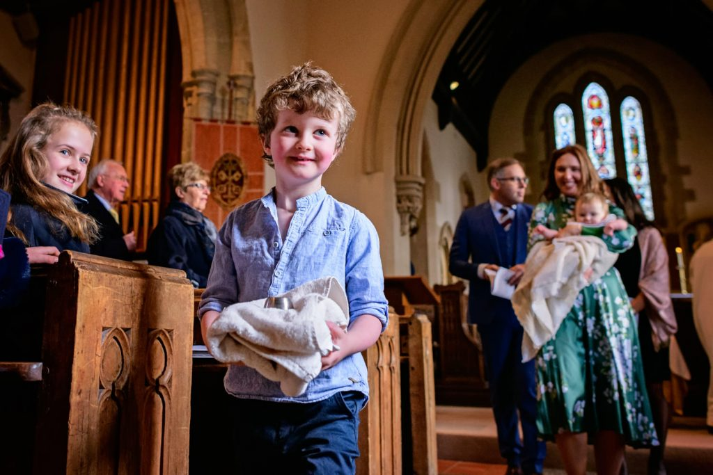 Boy carrying christening towel to the font
