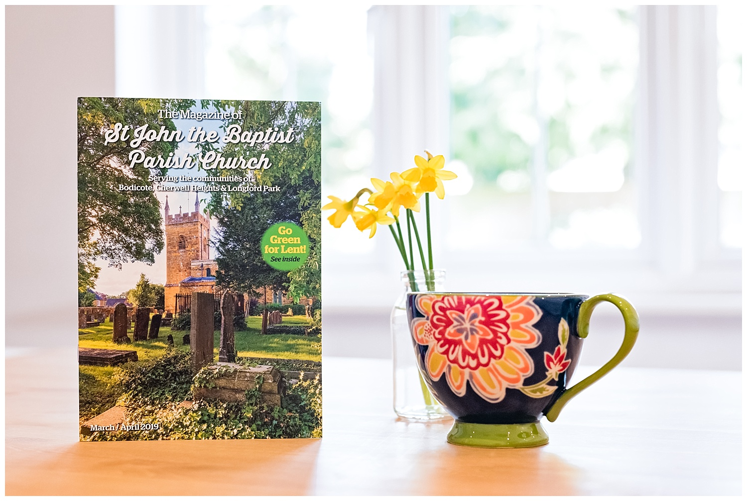 St John the Baptist Parish Church magazine stood next a cup of te and daffodils