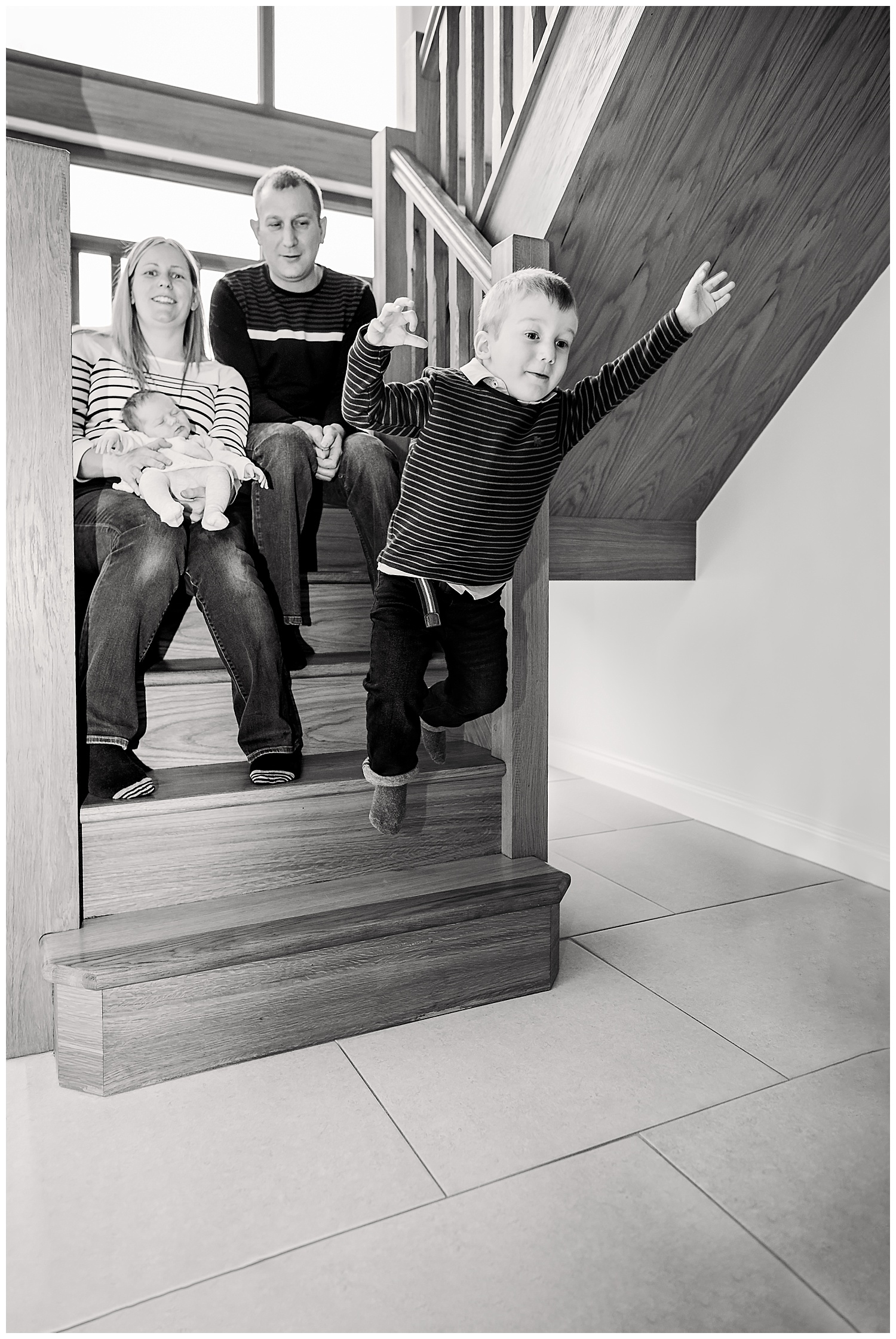 Happy toddler jumping off the stairs whilst the parents and baby sister watch