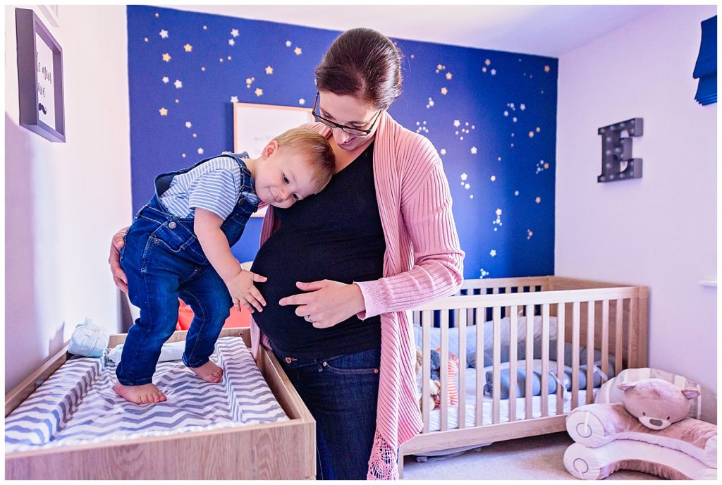Pregnant mother and toddler looking at the baby bump in the nursery