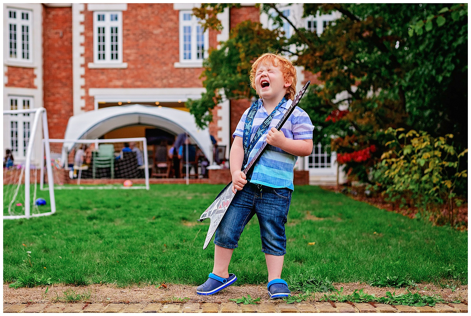 Party Photographer captures young boy stood with a guitar pretending to pull a rock star's face