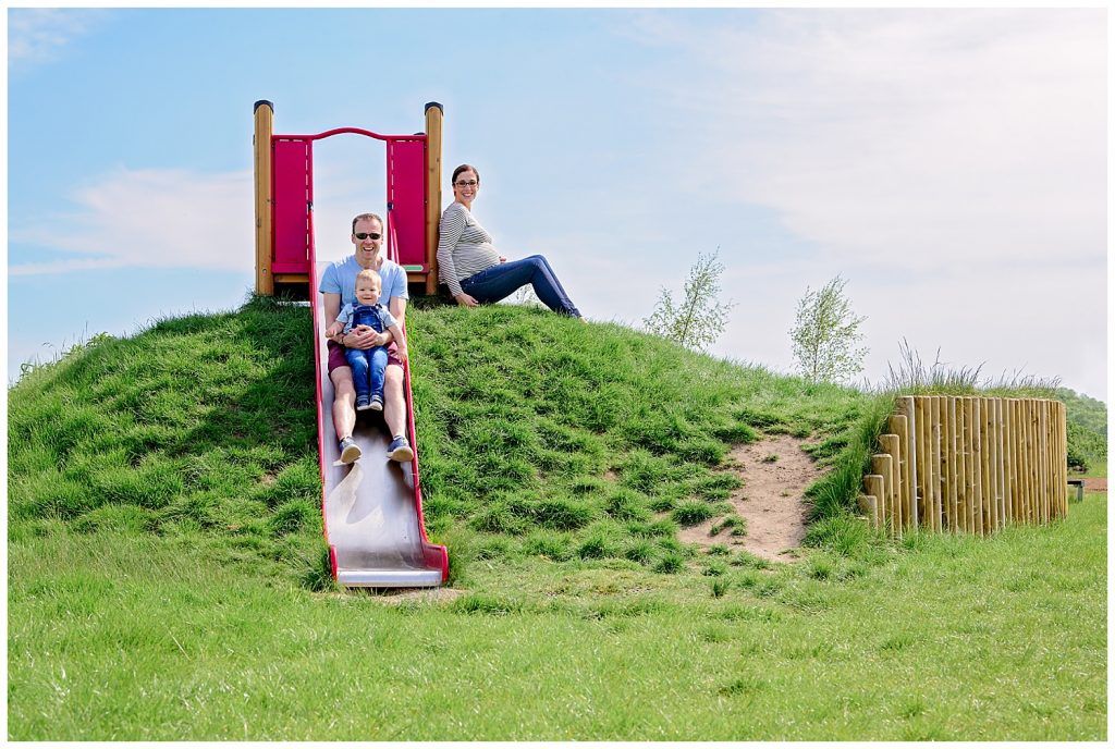 Maternity photo shoot. Faather and son sat on a slide with a toddler and heavily pregnant mother sat beside them.