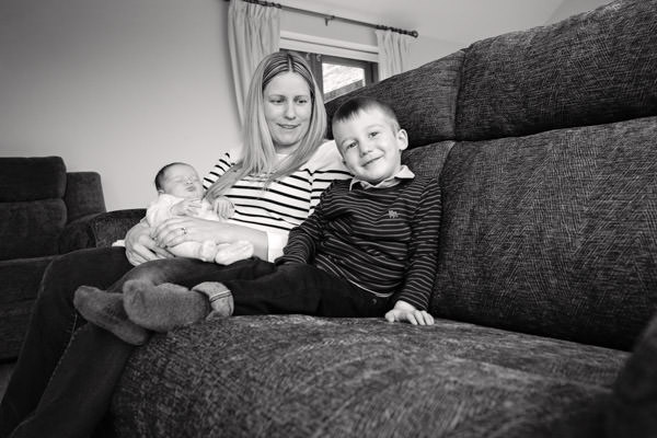Mother and boy sat on sofa with newborn baby