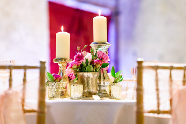 Golden table accesories including vases and candle sticks and pink flowers