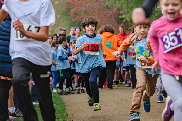 Boy sprinting towards the camera as part of a fun run