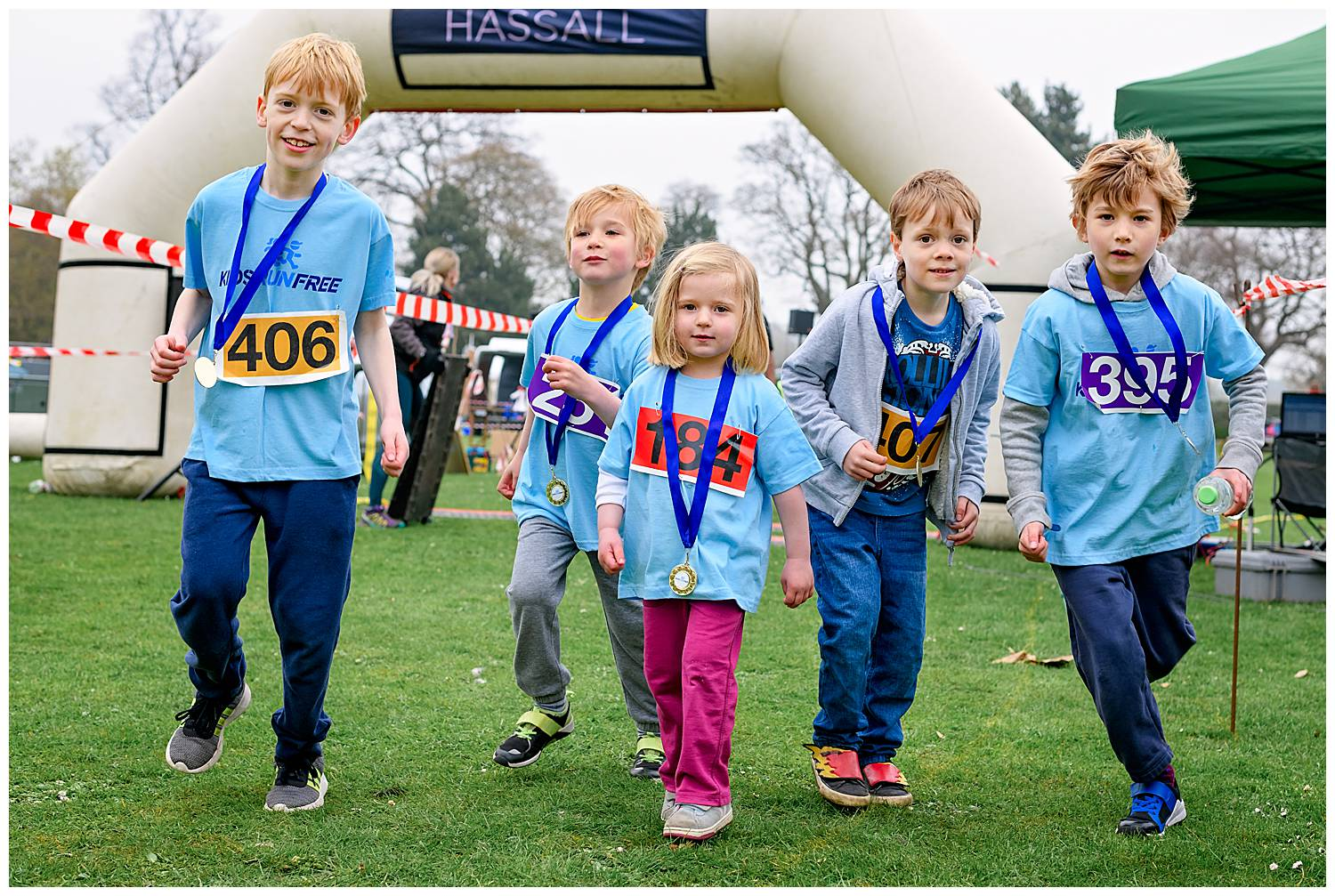 Alexandra Tandy Photography photo of children racing towards the camera with their medals