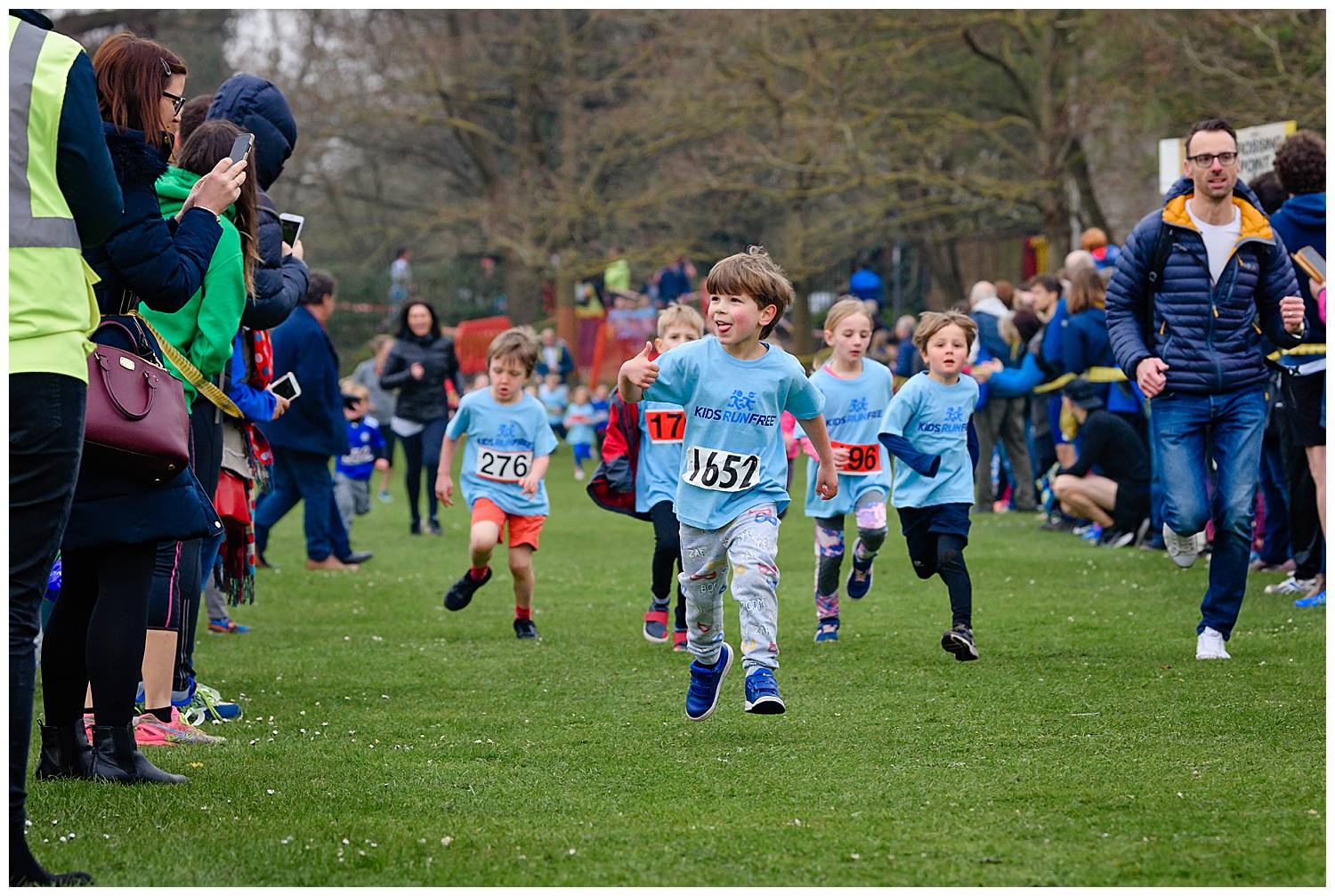Boy running and giving his thumbs up to his Mum as he run pasts