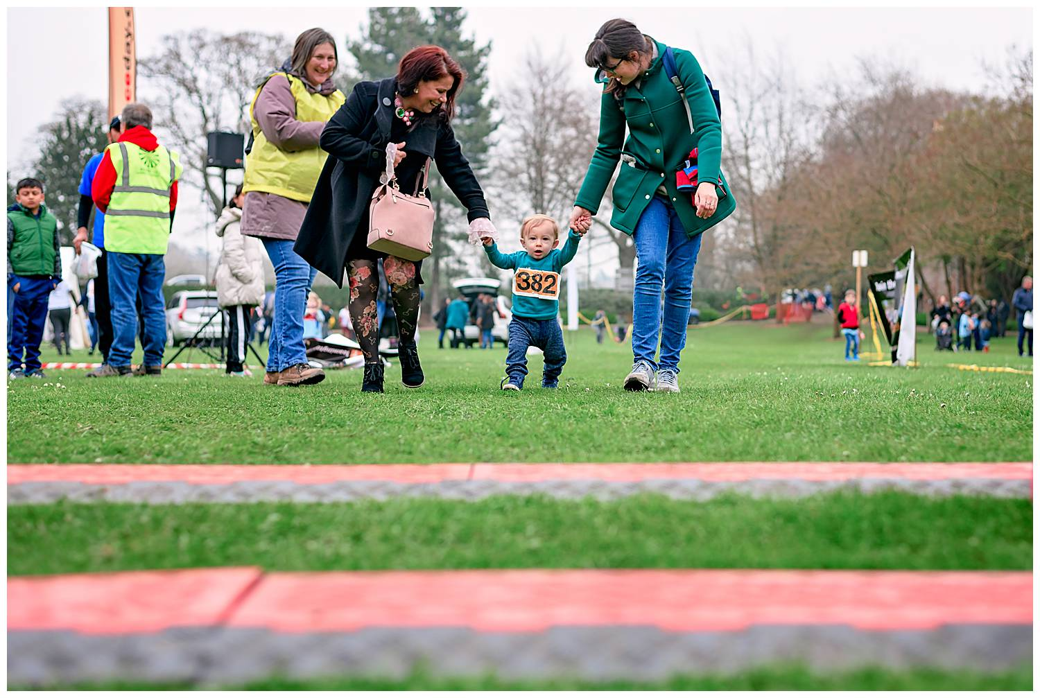 1 year old boy being helped by his mother and grandmother to cross the finish line of a 1k fun run