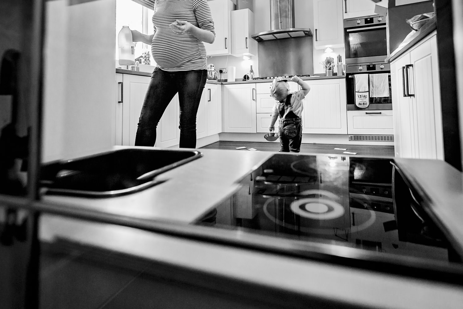 Boy toddler standing in the kitchen holding a play frying pan over his face