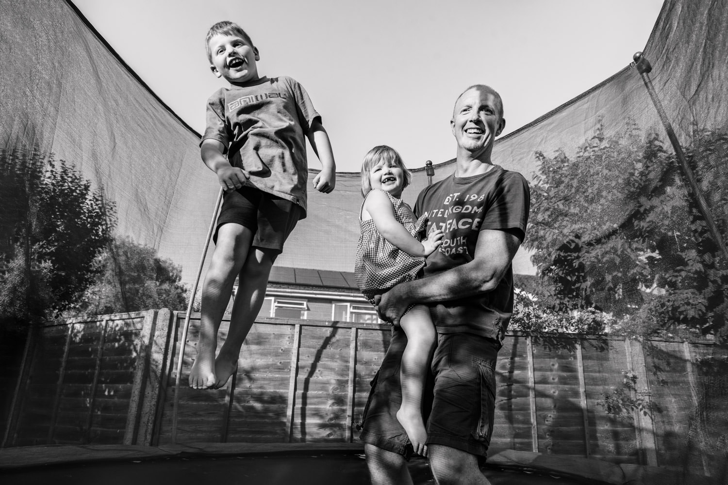 Photo shoot at home with Alexandra Tandy captures a boy jumping on a trampoline with his dad and sister