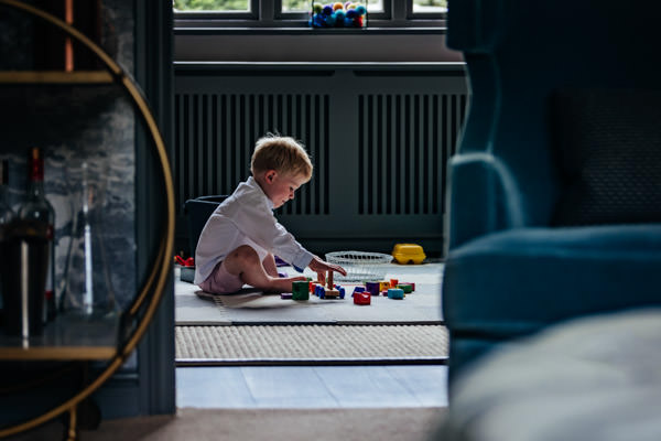 Boy sat by a window playing with his toys unaware that he's being photographed by Alexandra Tandy Photography