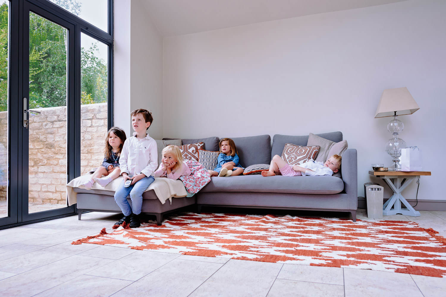 Five children relaxing on a giant grey corner sofa as they watch TV