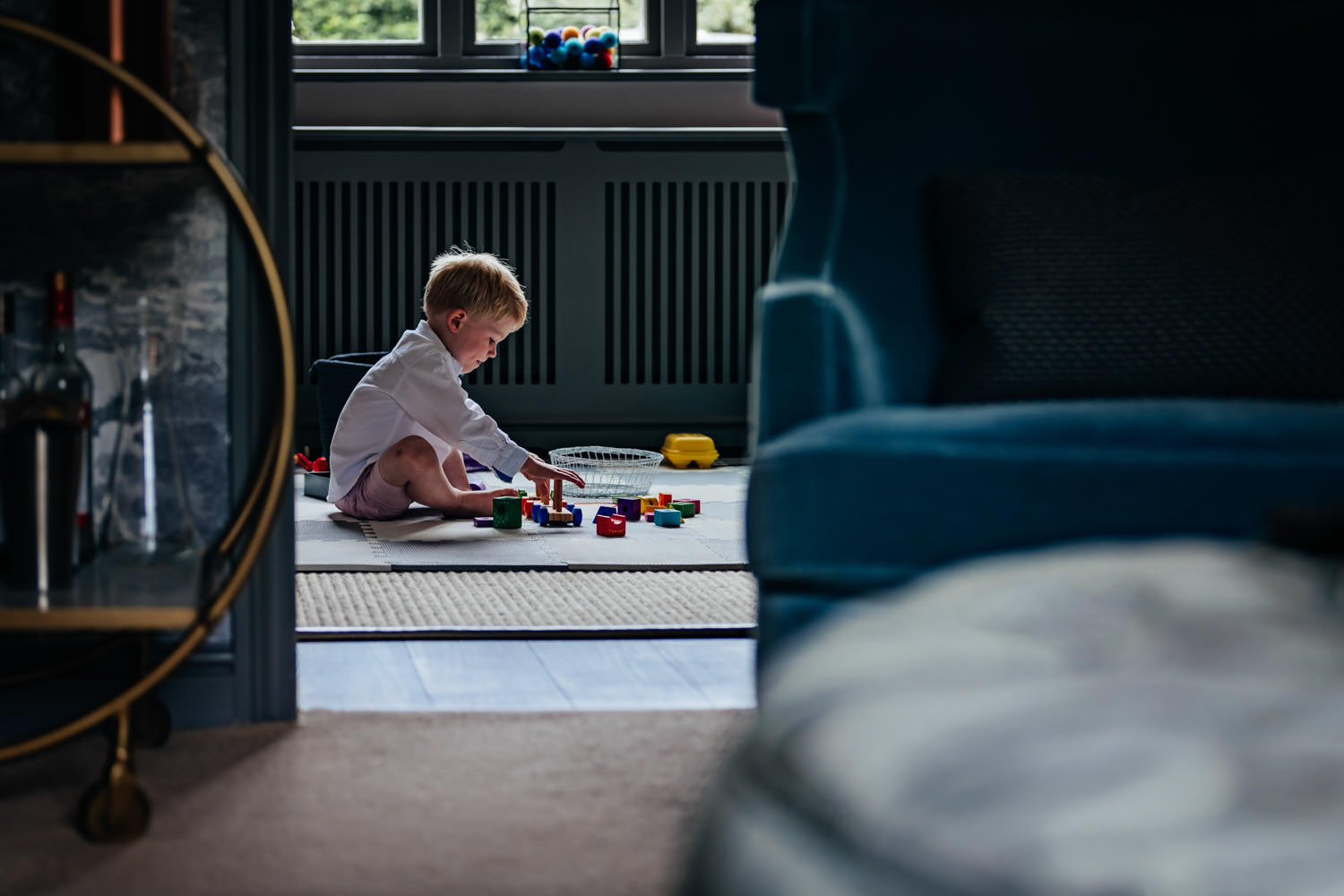 Little boy playing quietly by himself in the lounge