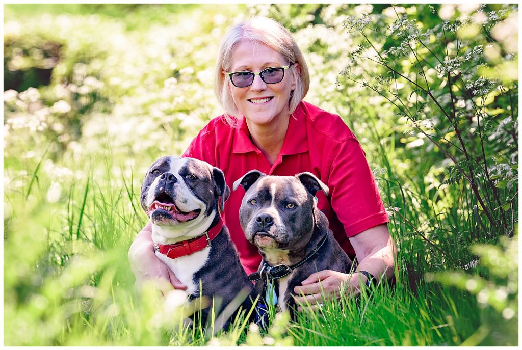 Headshot photo of a canine expert and first aid dog specialist sitting with her two dogs