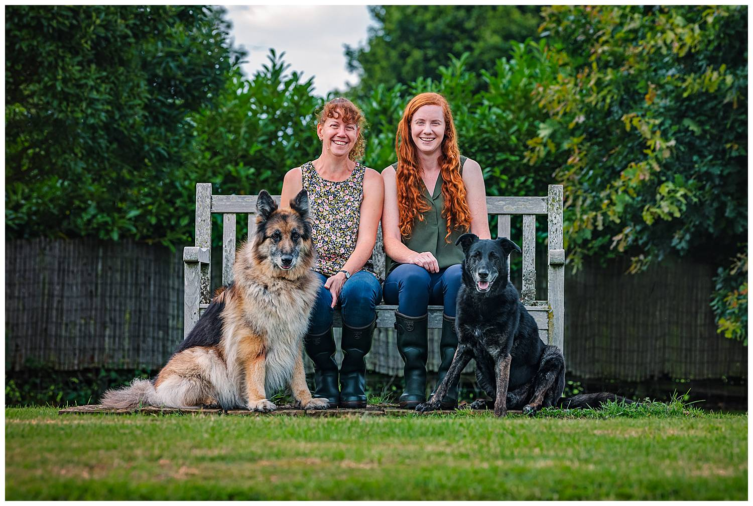 Mother and daughter sat on a wooden bench with two dogs