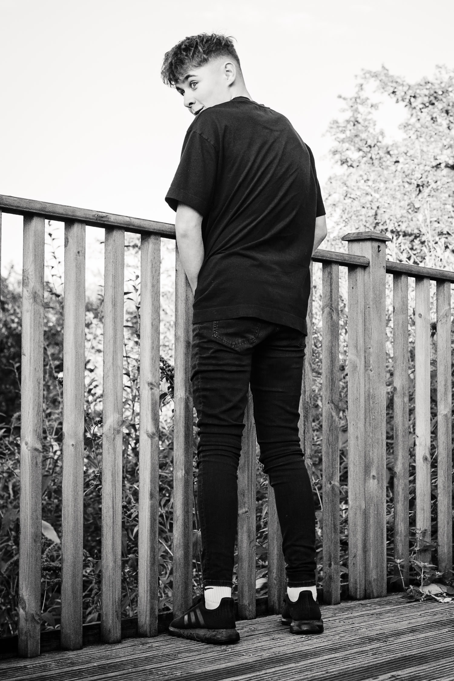 Black and white portrait of the back of a teenage boy pretending to wee through the railings.