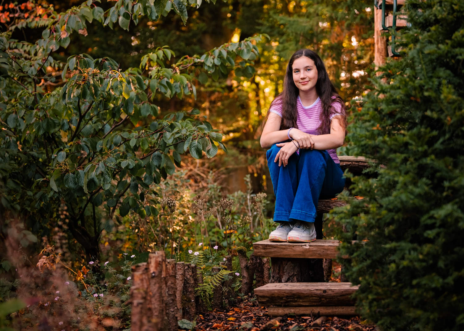 Teenage girl sat on wooden steps in an autumnal forest