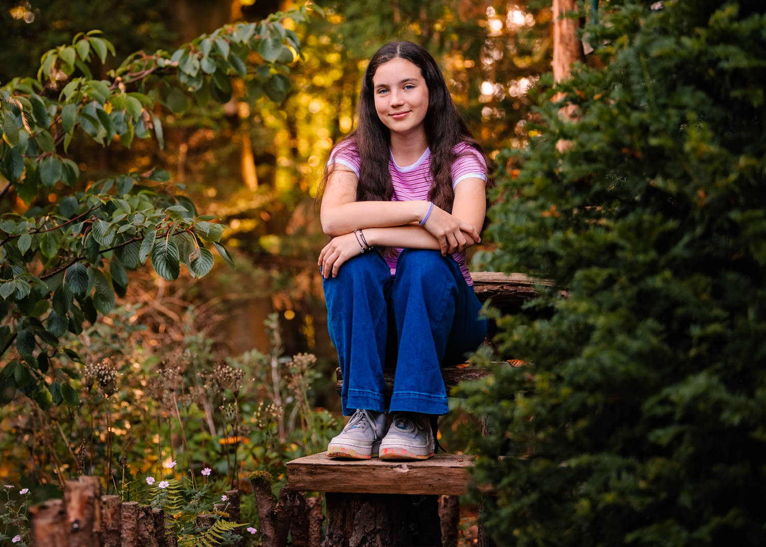 Teenage girl sat on wooden steps in an autumnal forest - photograph by Alexandra Tandy Photography