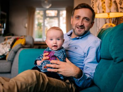 Photo of dad sat on sofa holding a smiling baby