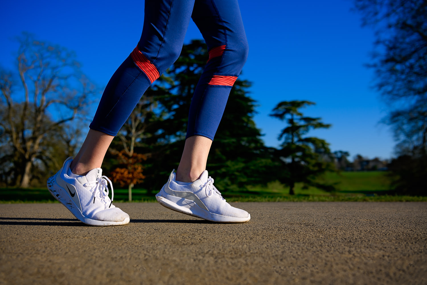 Close-up shot of a woman's feet  running along a path in white trainers