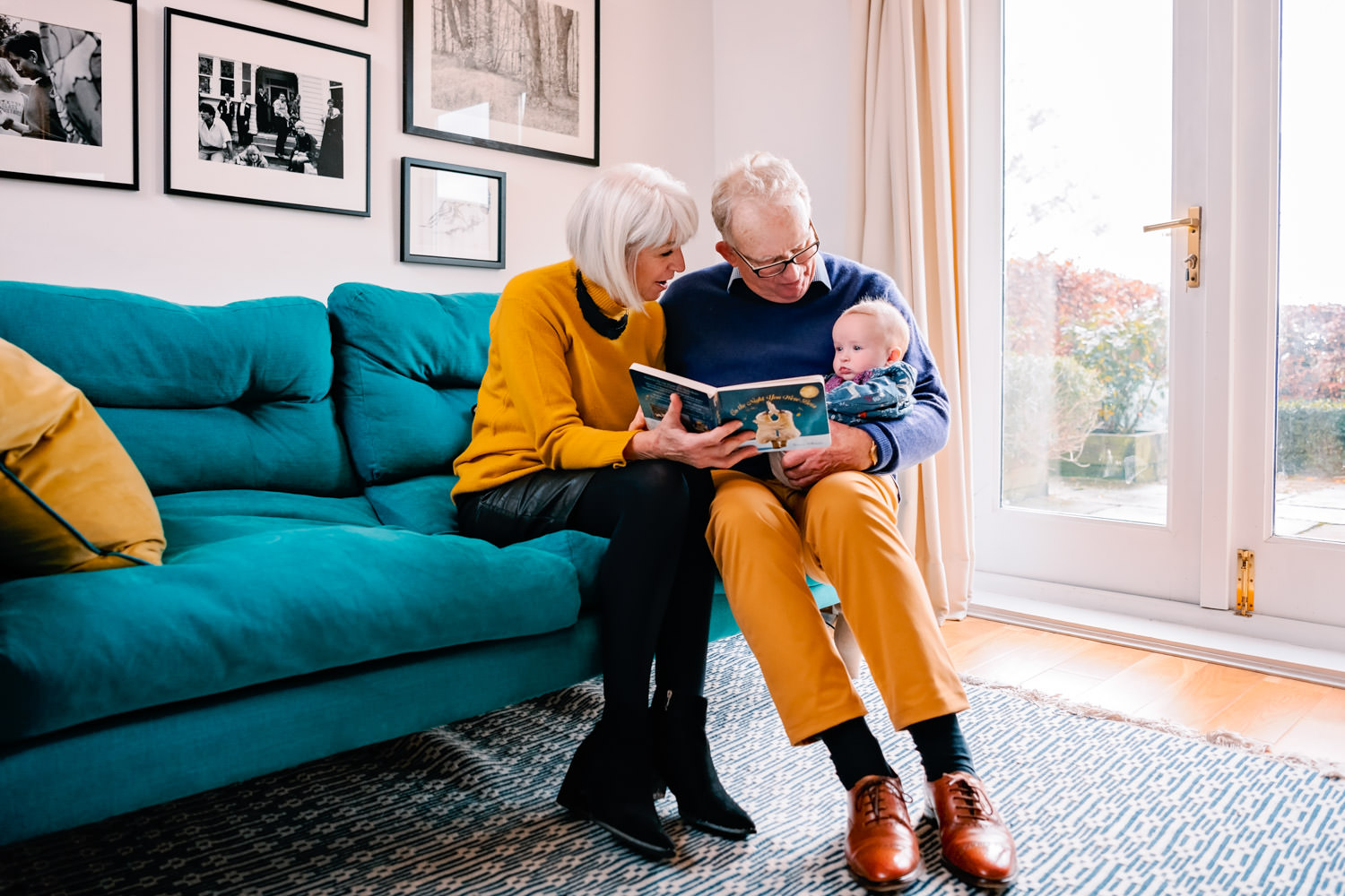 Grandparents sat on an emerald green sofa reading a book to their baby grandaughter