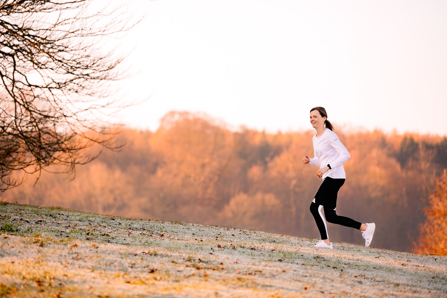Lady running up a grass hill on a frosty day with autumnal leaves in the background